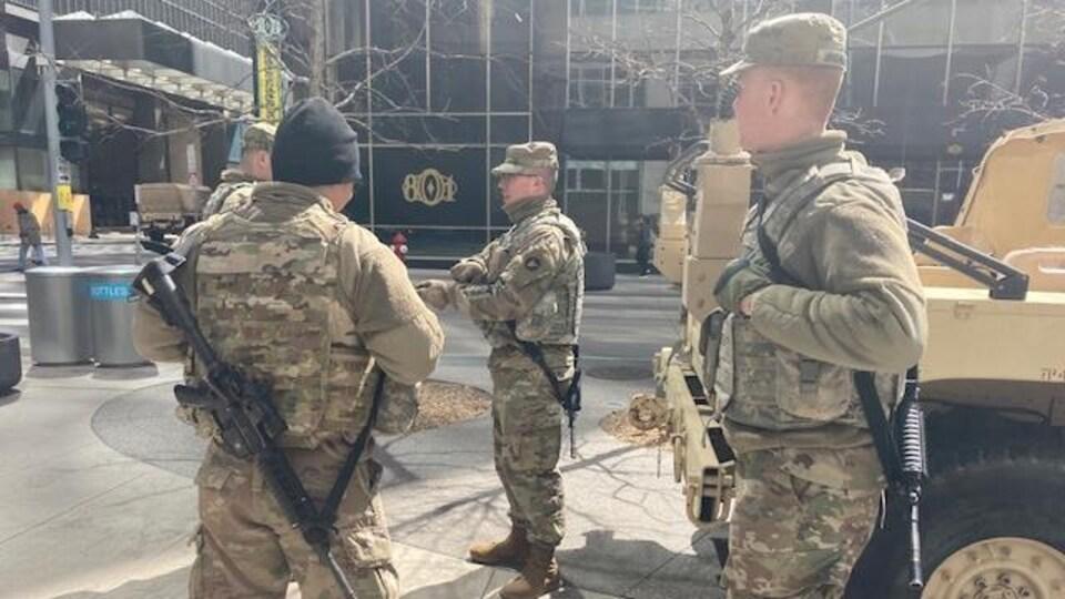 Des hommes en treillis, armés de fusils mitrailleurs, discutent à côté d'un véhicule blindé.