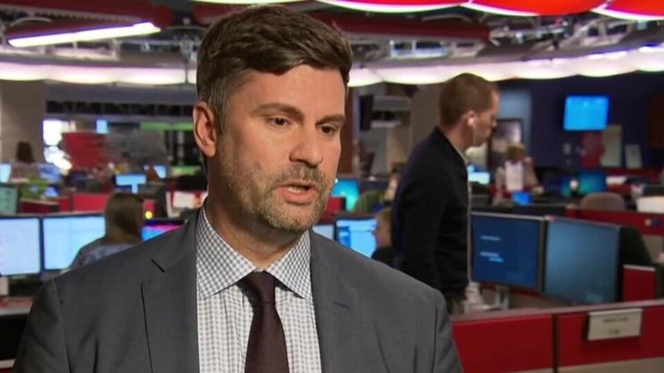 Un homme qui porte une veste grise et une cravate.