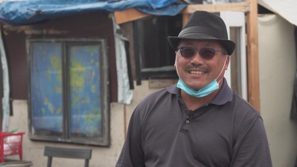 Derrick Soo porte chapeau et lunettes fumées. Il a baissé son masque.