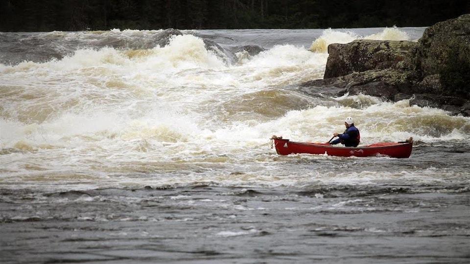 Un canoteur pagaie au bas d'un rapide de la rivière Magpie.