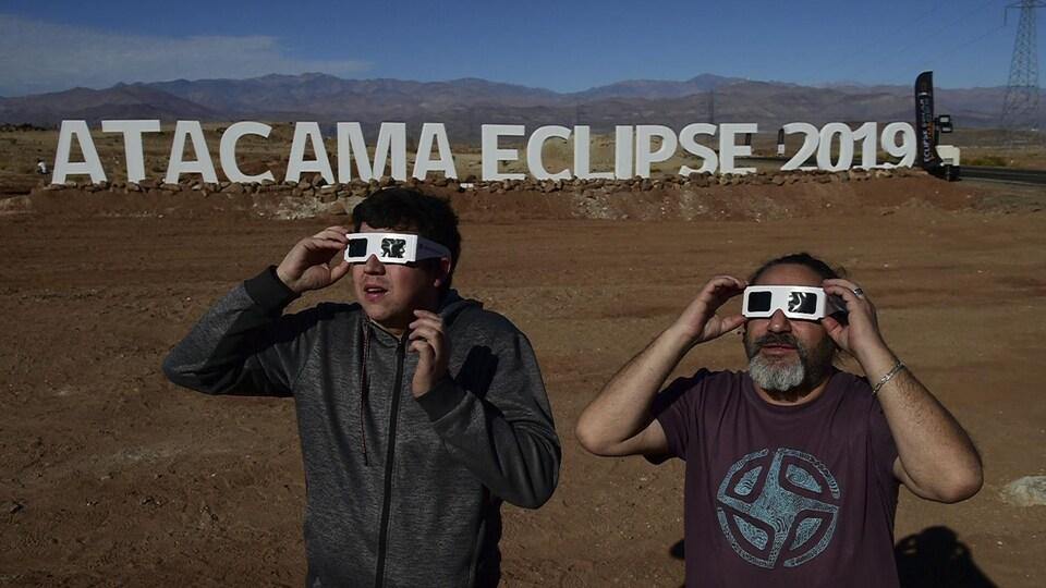 Dans le désert, des touristes essaient les lunettes spéciales en regardant vers le soleil. Derrière eux, d'immenses lettres ont été installées. On peut y lire : ATACAMA ECLIPSE 2019.