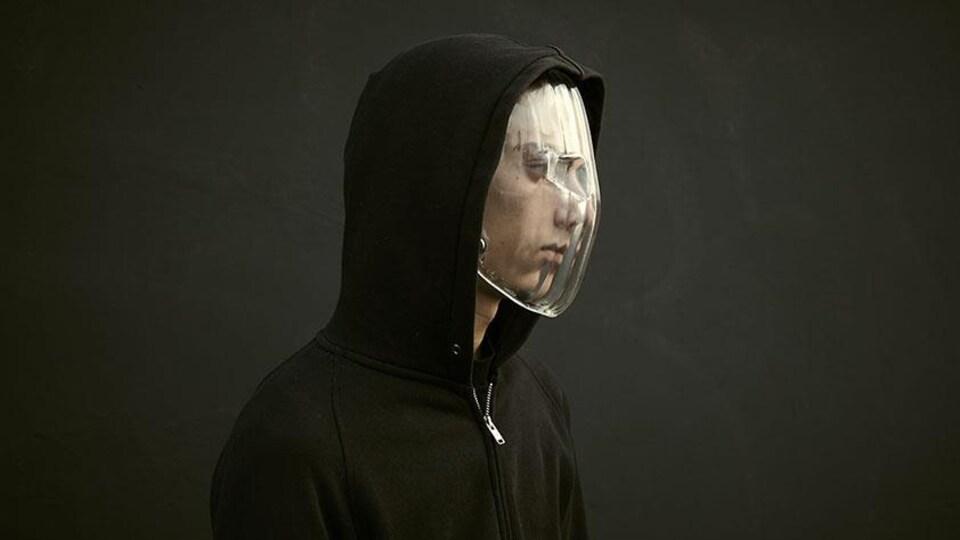 Un homme avec un capuchon noir porte un masque en plastique transparent.