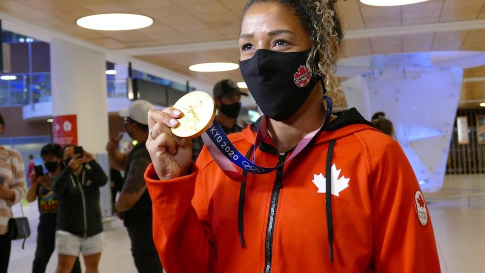 Desiree Scott montre sa médaille d'or. Elle est habillée en rouge, aux couleurs de l'équipe canadienne.