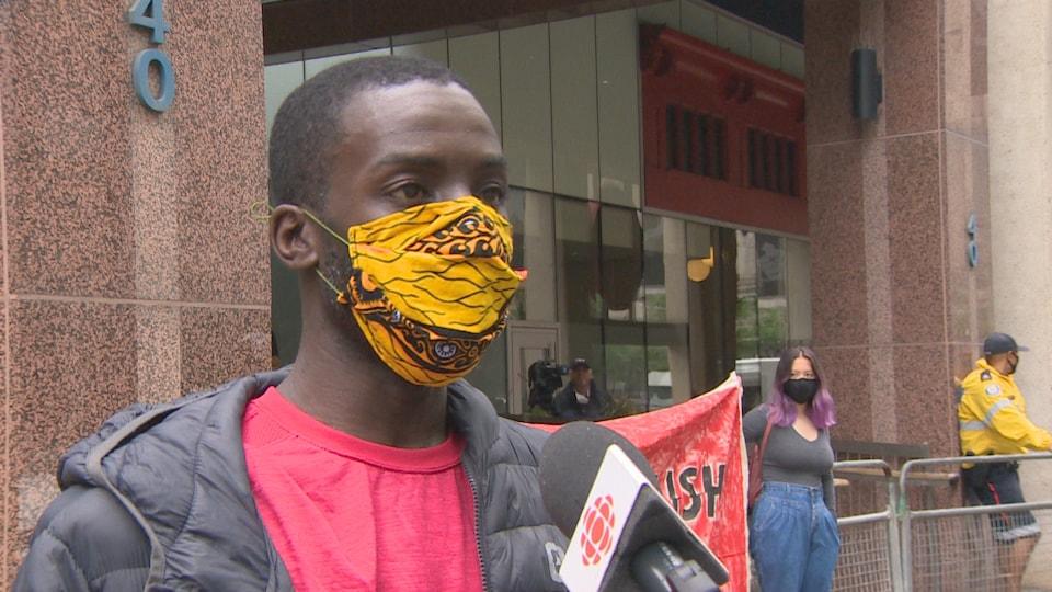 Desmond Cole portant un masque en entrevue au micro d'un journaliste lors de la manifestation devant le Commissariat du Service de police de Toronto.