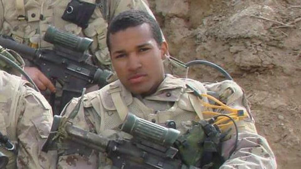 Lionel Desmond en uniforme militaire assis en Afghanistan, son fusil d'assaut repose sur ses genoux.