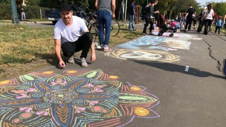 Plusieurs personnes dessinent sur une piste asphaltée.