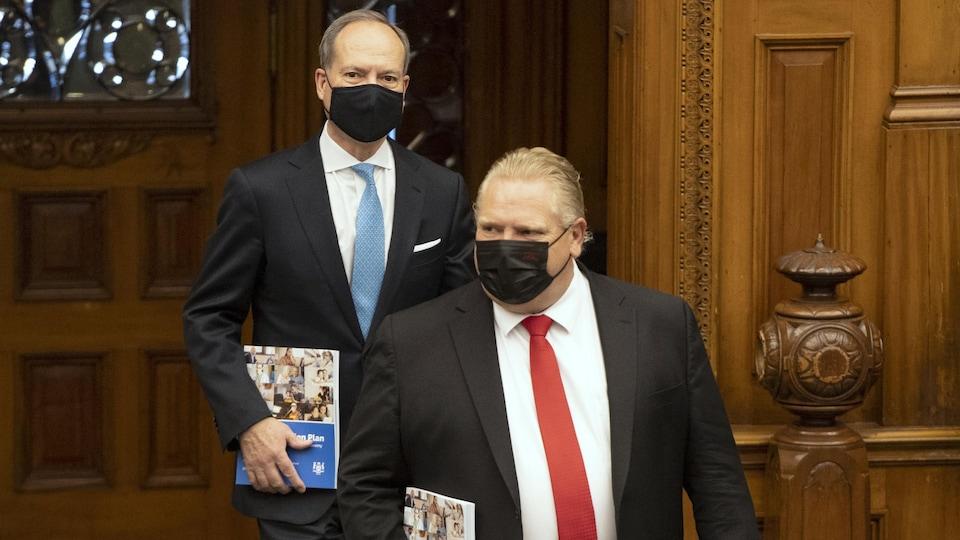Deux hommes portant un masque noir rentrent dans une salle.