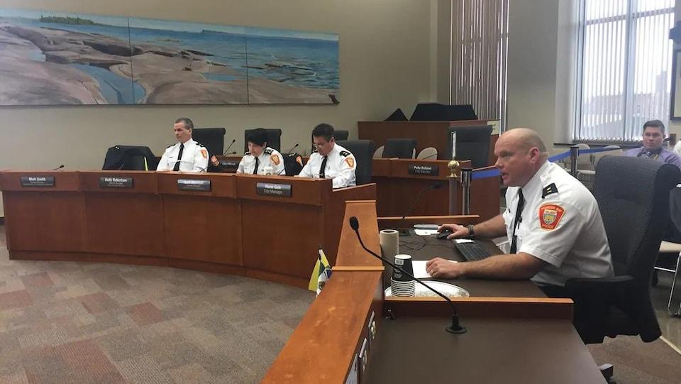 Des agents de police en uniforme assis derrières des bureaux.