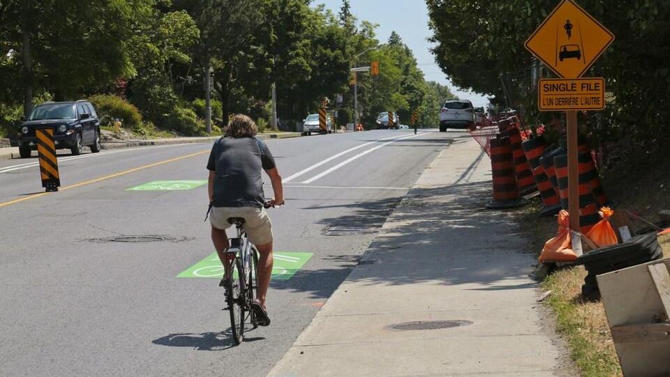 Un cycliste roule dans la rue à proximité de voitures et de cônes oranges.