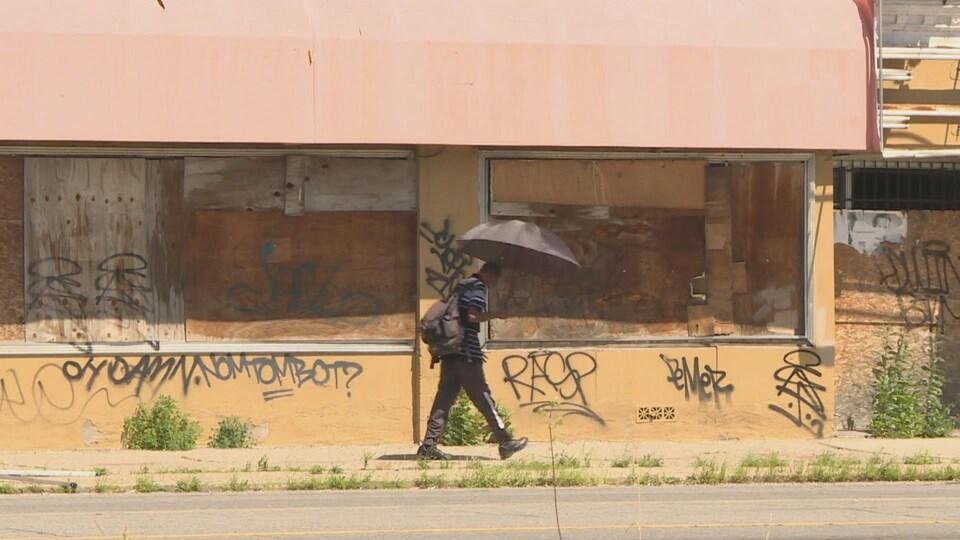 Un homme marche avec un parapluie noir devant un mur de graffitis.
