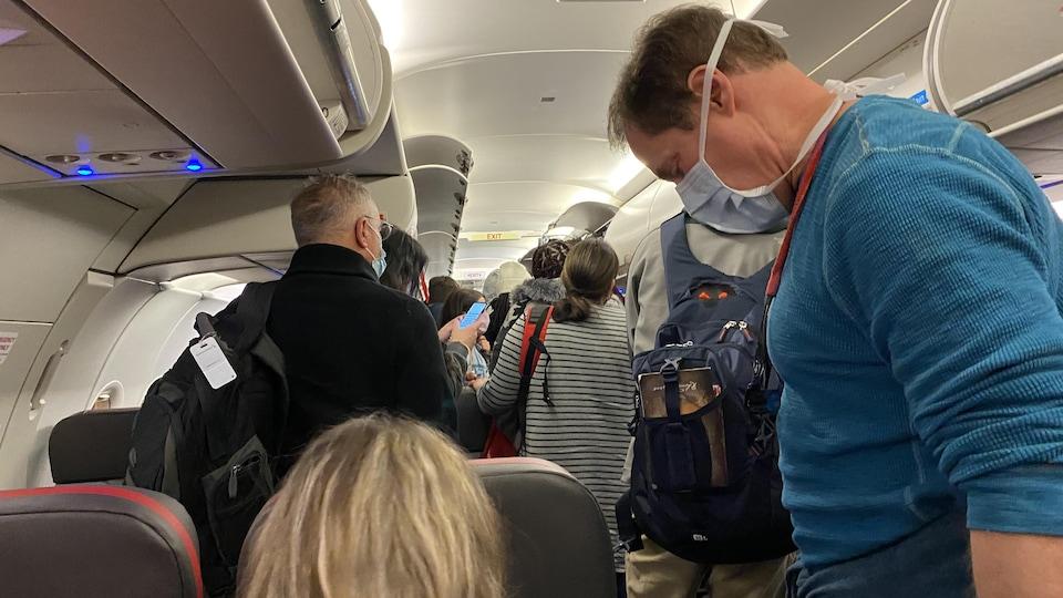 Des gens qui se précipitent pour récupérer leurs bagages après l'atterrissage d'un avion.
