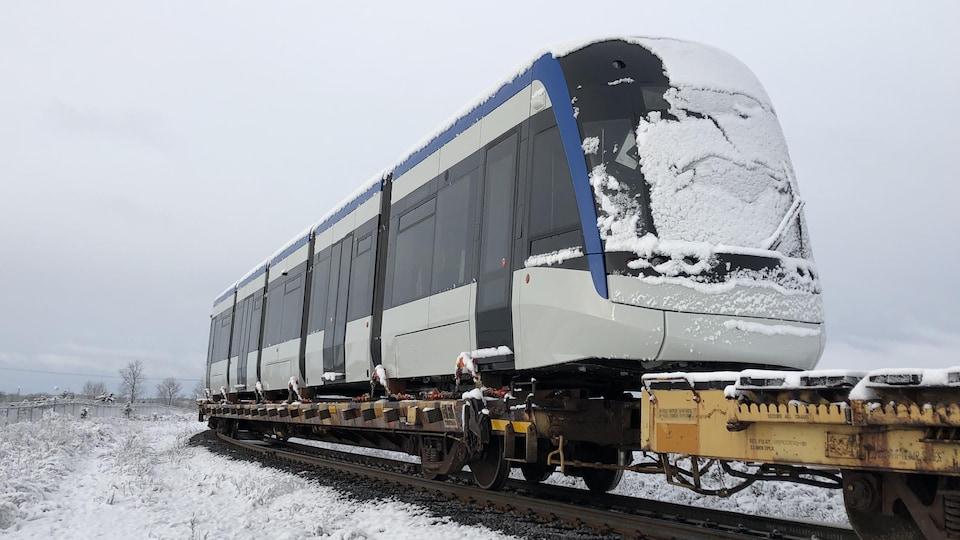 On voit le train solidement attaché sur un wagon sur rails.