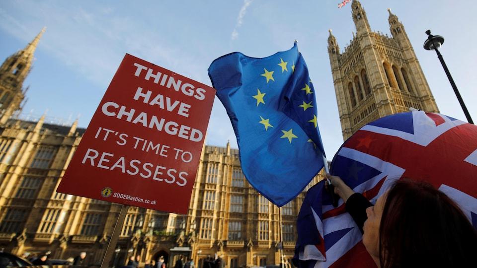 «Les choses ont changé. Il est temps de réévaluer», peut-on lire sur une pancarte installée devant le Parlement britannique, tout près d'une femme brandissant des drapeaux du Royaume-Uni et de l'Union européenne.