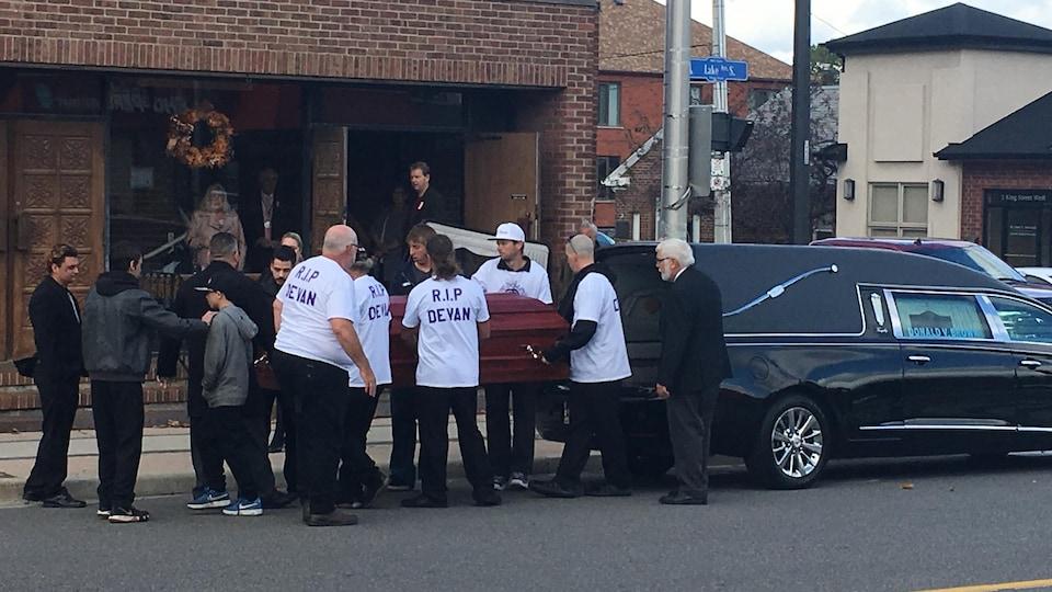 """Des personnes portant des T-shirts où il est écrit """"RIP Devan"""" transportent un cercueil devant un établissement."""