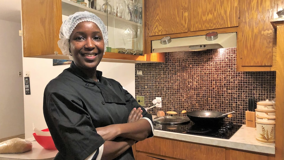 Une femme en tablier noir et cheveux couverts d'un filet blanc dans sa cuisine