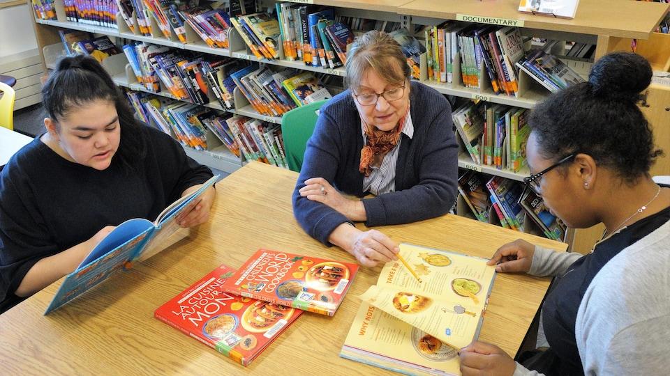 Deux filles et une dame au centre regardent des livres de cuisine, à une table, devant des rayons de bibliothèque.