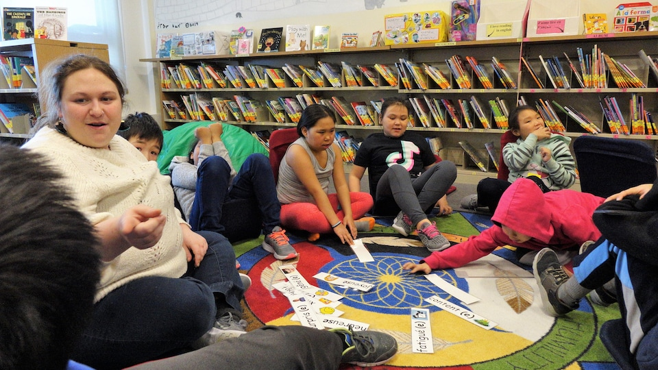 Un groupe d'élèves assis par terre à la bibliothèque avec leur enseignante .