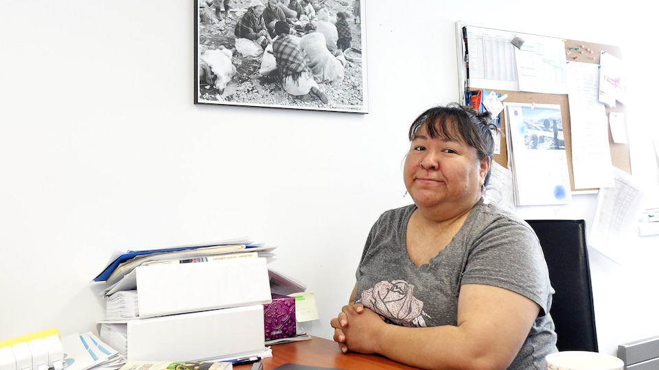 Une femme assise à son bureau avec au mur une photo en noir et blanc d'ancêtres inuit occupés à fabriquer un canot.