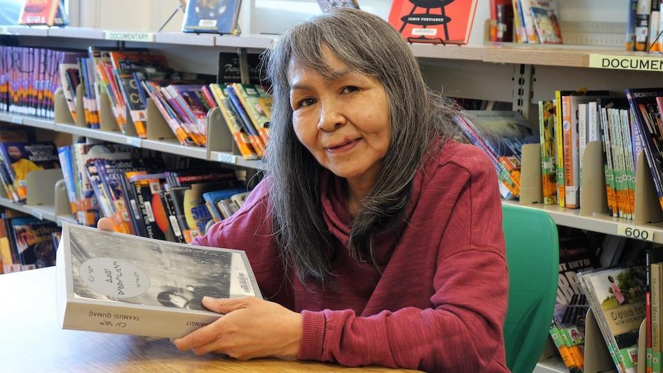 Une femme aux cheveux longs gris tient un livre dans ses mains, assise à une table dans une bibliothèque
