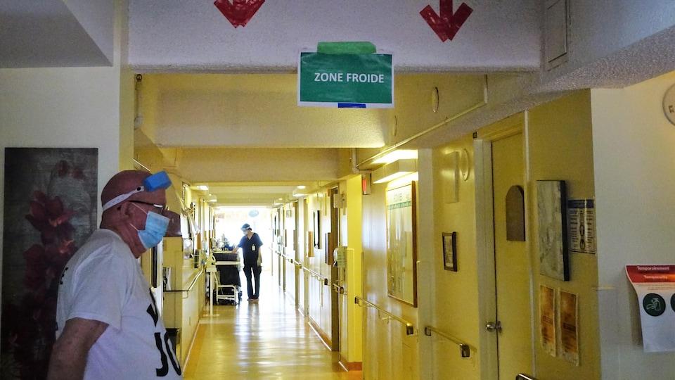 """Une affiche verte """"zone froide"""" en haut de l'entrée d'un couloir du CHSLD Nazaire-Piché à Lachine, avec un monsieur à gauche et la silhouette noire d'une préposée au fond."""
