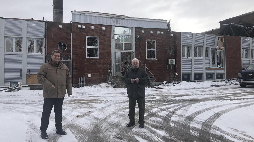 Carl Dufour et Jean-Guy Dufour devant la structure du bâtiment incendié.