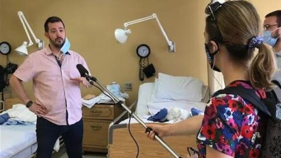 Un homme debout dans une salle de formation pour préposés en CHSLD interviewé par la journaliste sur le côté droit.