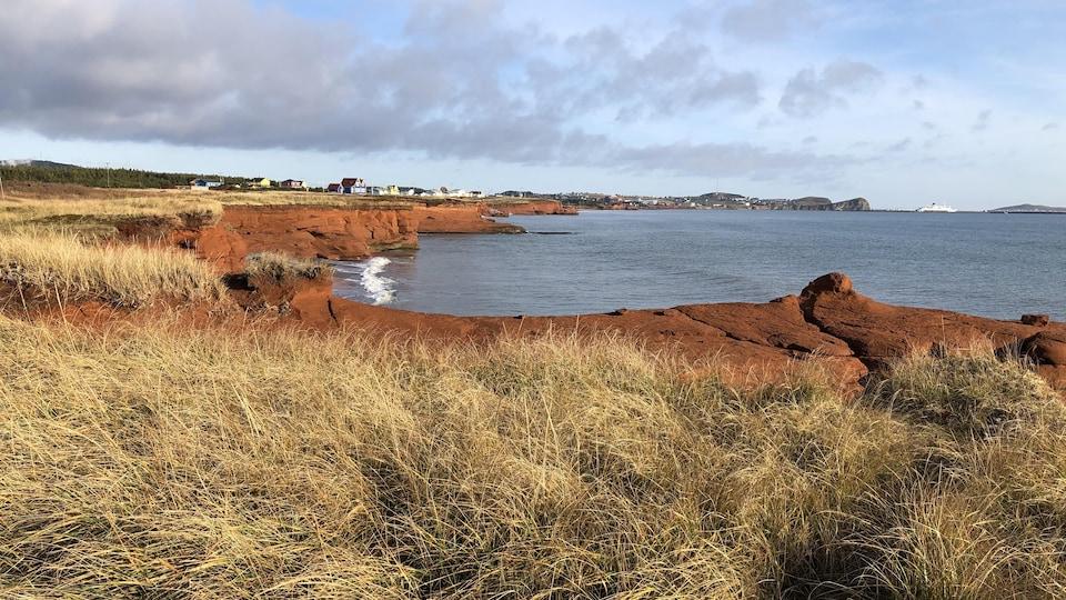 Des falaises sur le bord de la mer. Au loin, des maisons et un navire.