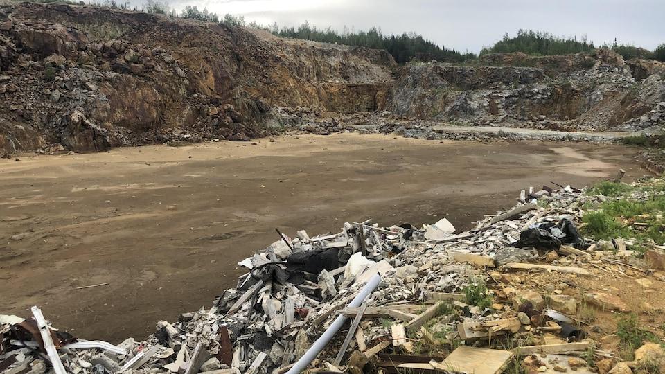 Grand trou creusé dans un rocher entouré de débris.