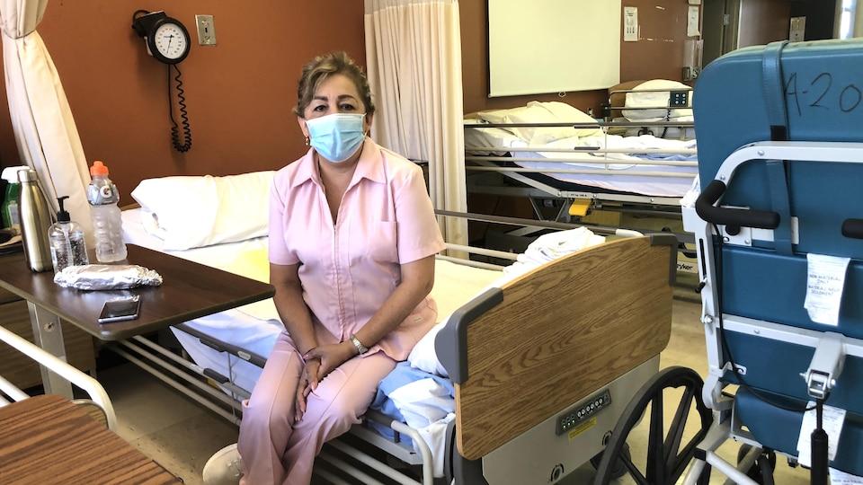 Une dame en rose avec un masque assise sur un lit.