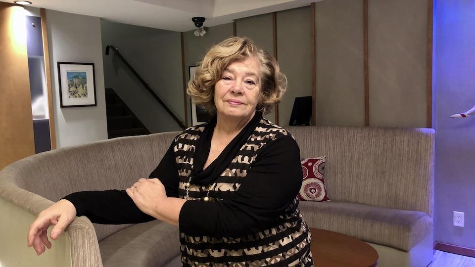 Une dame debout appuyée contre un divan