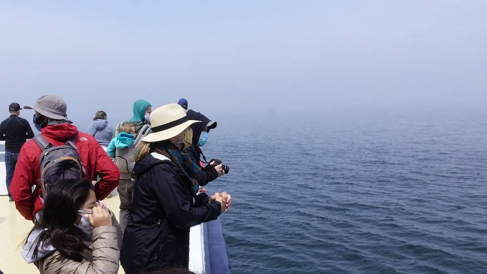 Femme avec un chapeau et jeune fille avec un masque regardent l'eau depuis le pont d'un navire.