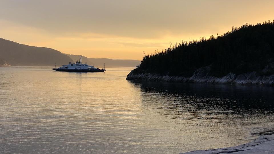 Un traversier sur l'eau, au soleil couchant.
