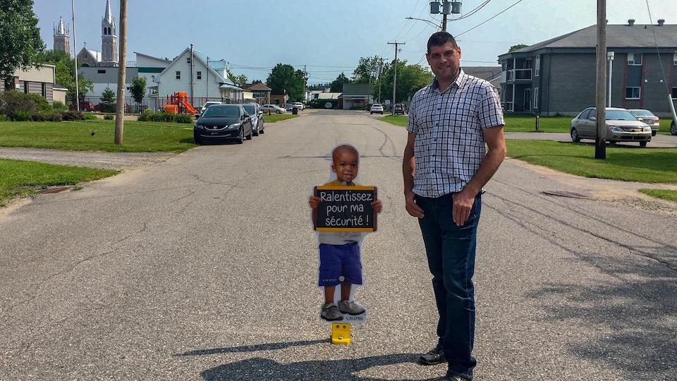 Affiche d'enfant et le directeur général à ses côtés, dans la rue.