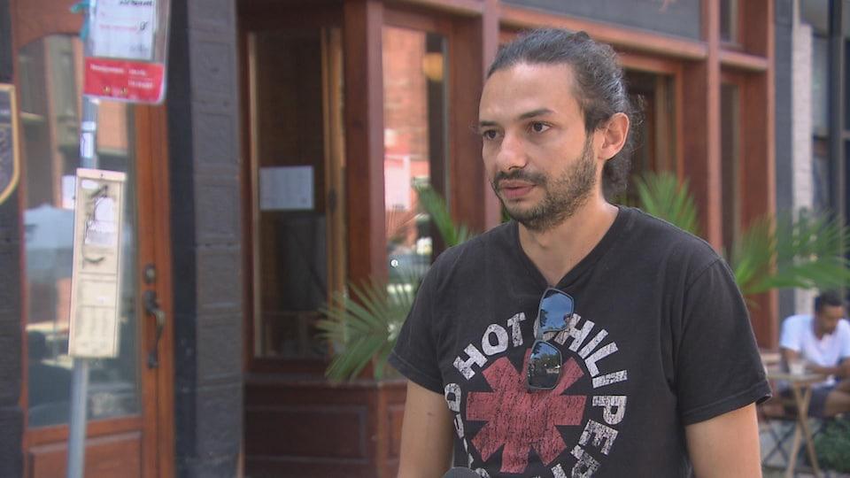 Dhirar Mouhli est debout sur le trottoir devant son commerce.