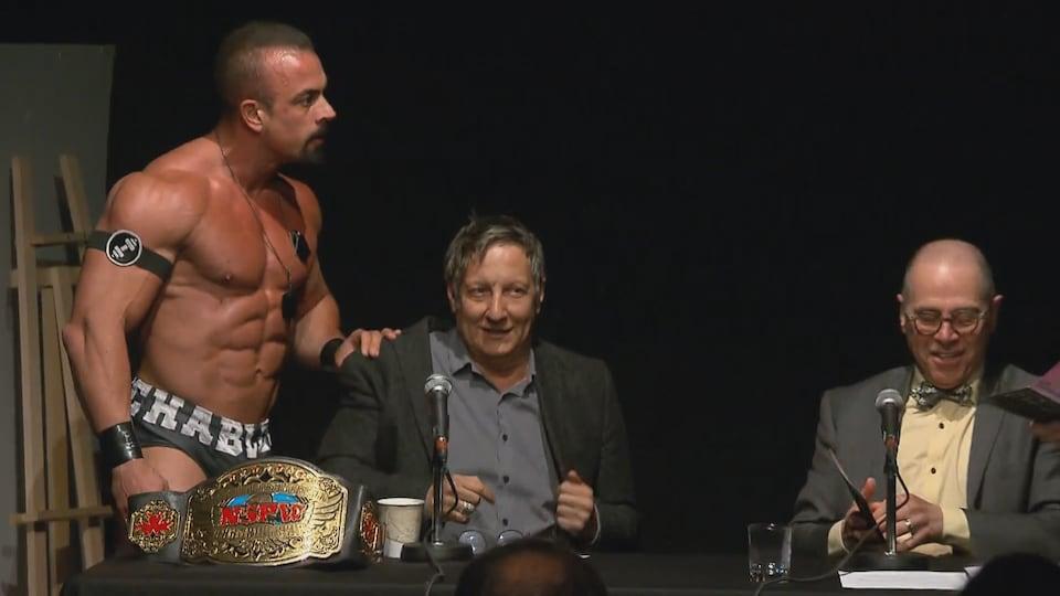 Un lutteur est debout sur une scène et pose sa main sur l'épaule de Robert Lepage.