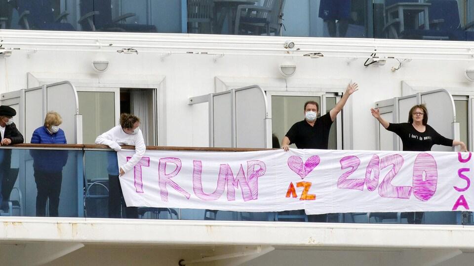 Des passagers portant des masques regardent un homme et une femme saluer derrière une bannière sur laquelle ils ont peint un cœur et l'inscription : « Trump 2020, USA ».