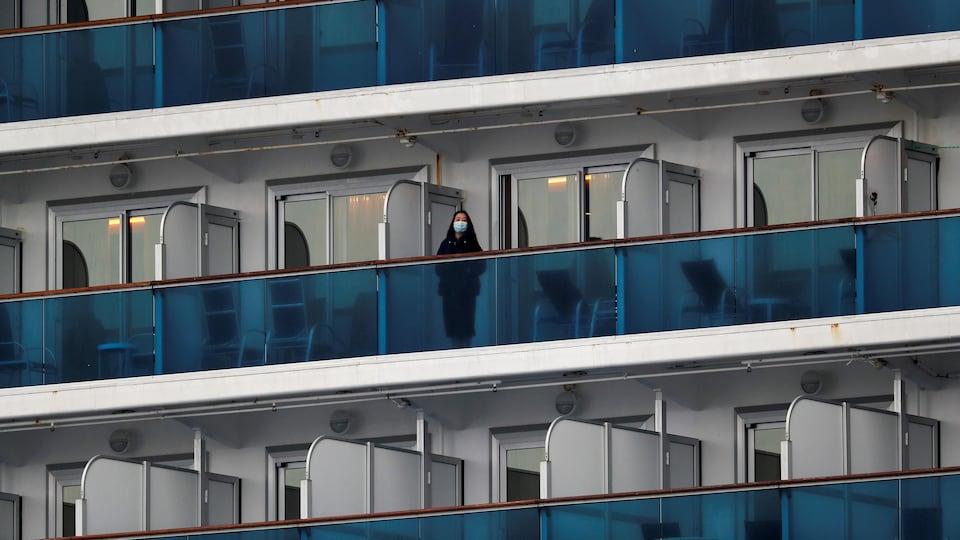 Une passagère portant un masque se trouve sur le balcon d'un bateau de croisière.