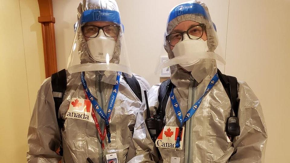 Deux personnes debout portent des équipements de protection, dont des masques et des gants. Des drapeaux canadiens sont cousus sur leur combinaison.