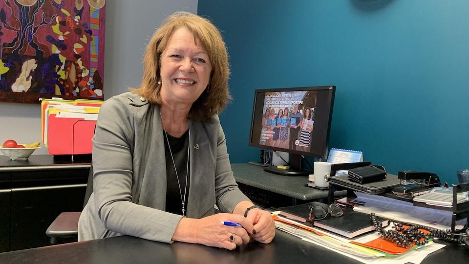 Diane Dallaire pose derrière son bureau, souriante.