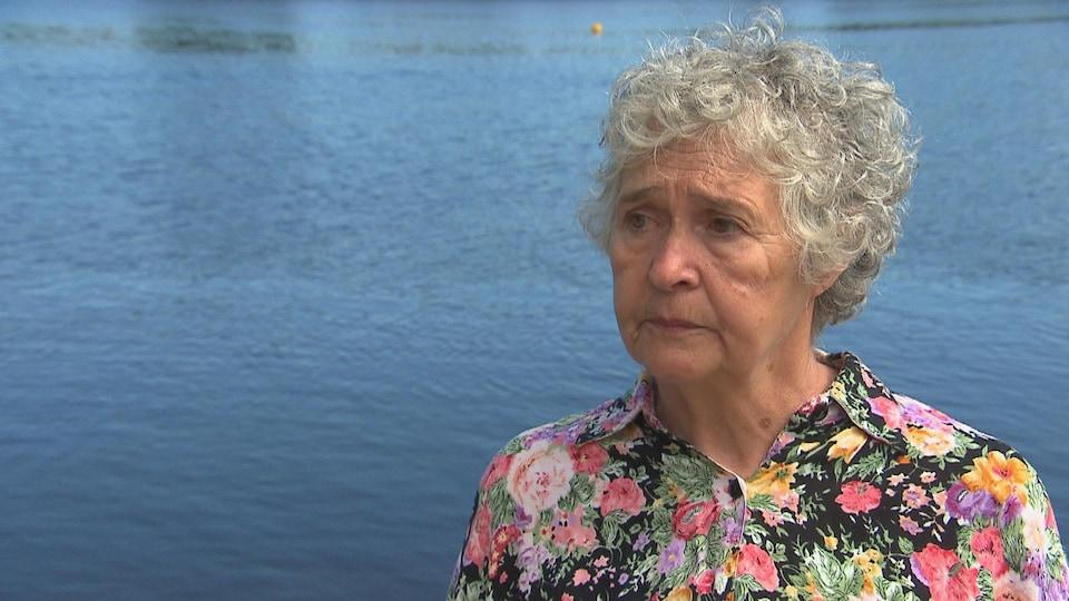 Une femme âgée devant la rivière Saint-Maurice.