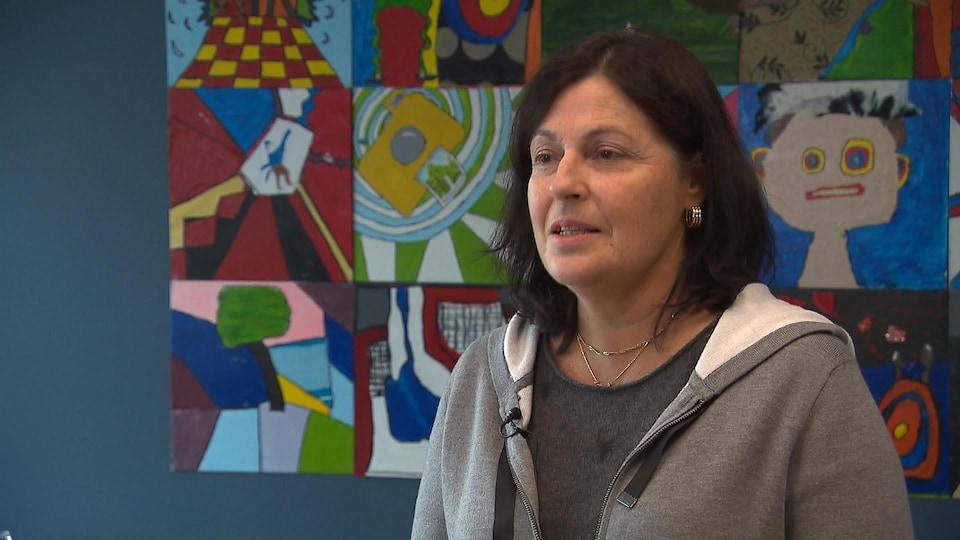 Mme Lamarche-Venne en entrevue dans son bureau, devant un montage de dessins d'élèves.