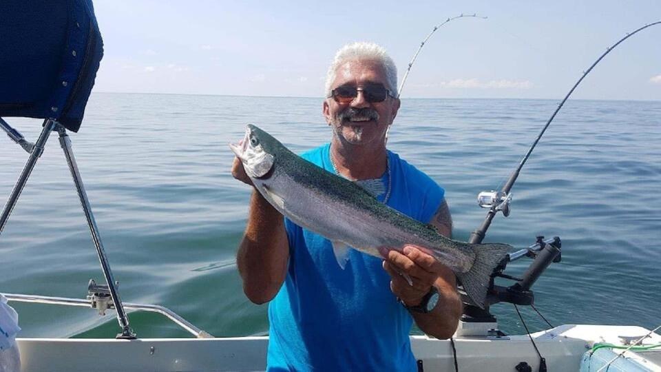 Un pêcheur souriant montre un poisson.