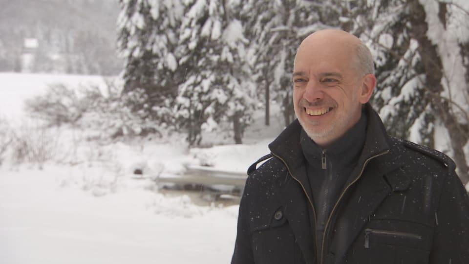 L'homme sourit. Il est à l'extérieur et de la neige tombe.