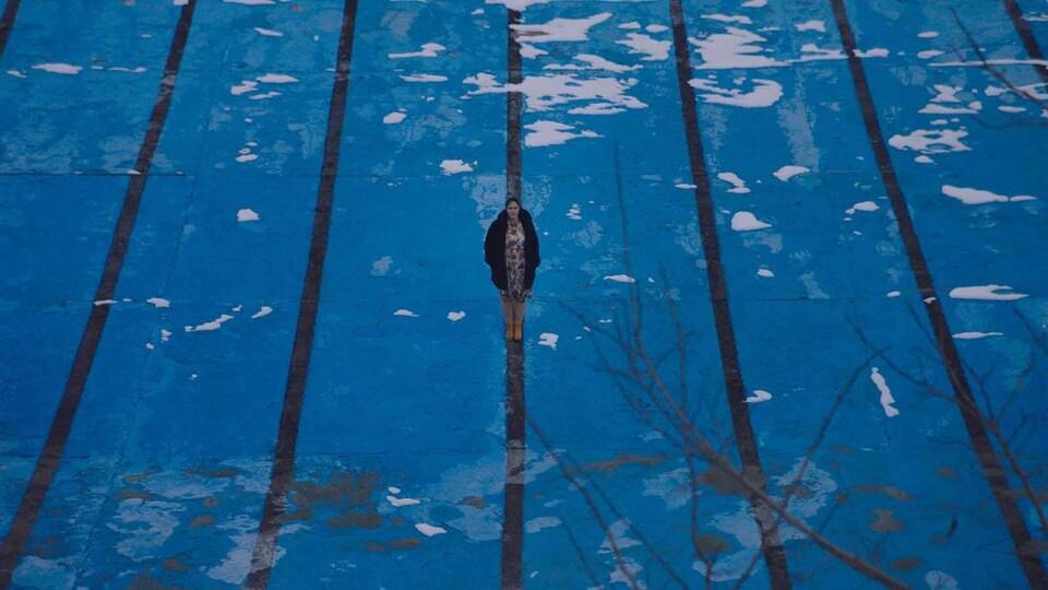 Une femme se tient debout, en plein milieu d'une piscine, comme si elle marchait sur l'eau.