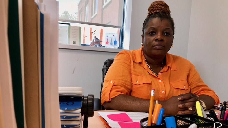 Laurence Makanda assise dans son bureau, regarde la camera.