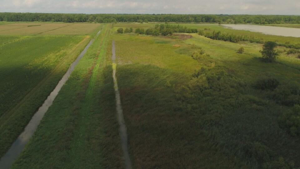 Un canal recueille l'eau le long d'une terre.