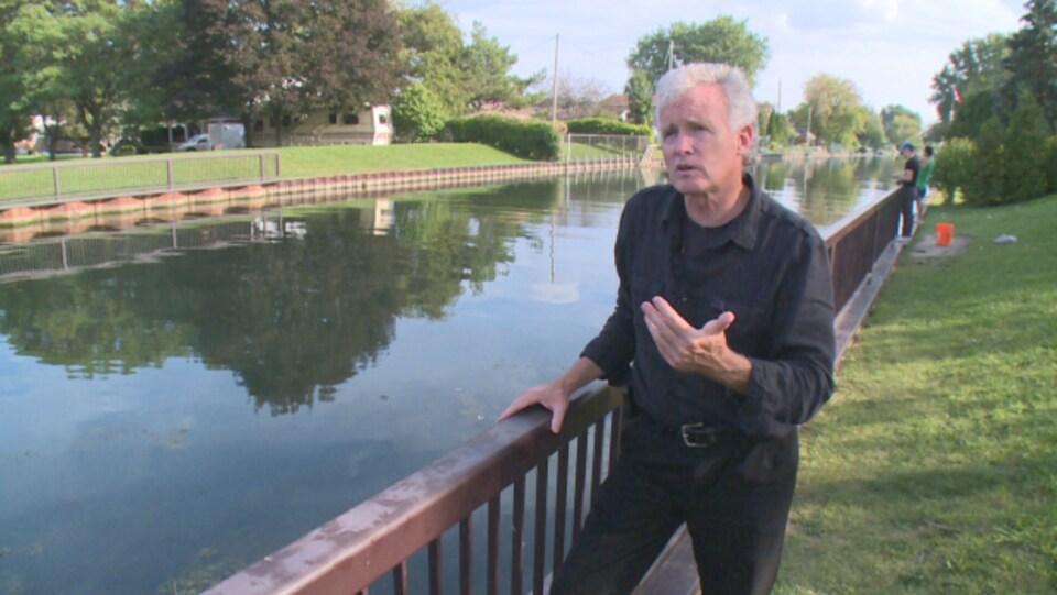 Un homme habillé en noir par à la caméra sur le bord de l'eau d'un canal.