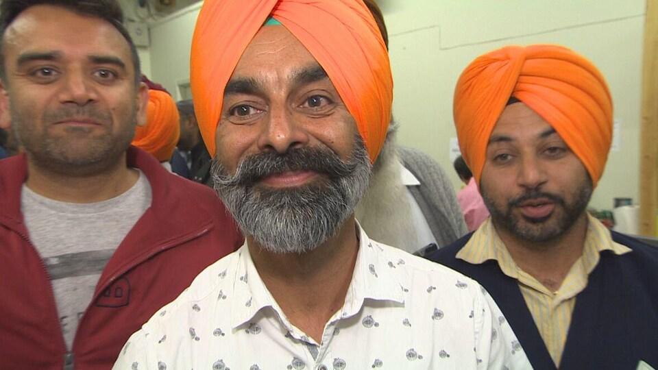 Un homme, qui a un turban orange, sourit. Il est entouré de deux autrs  hommes.