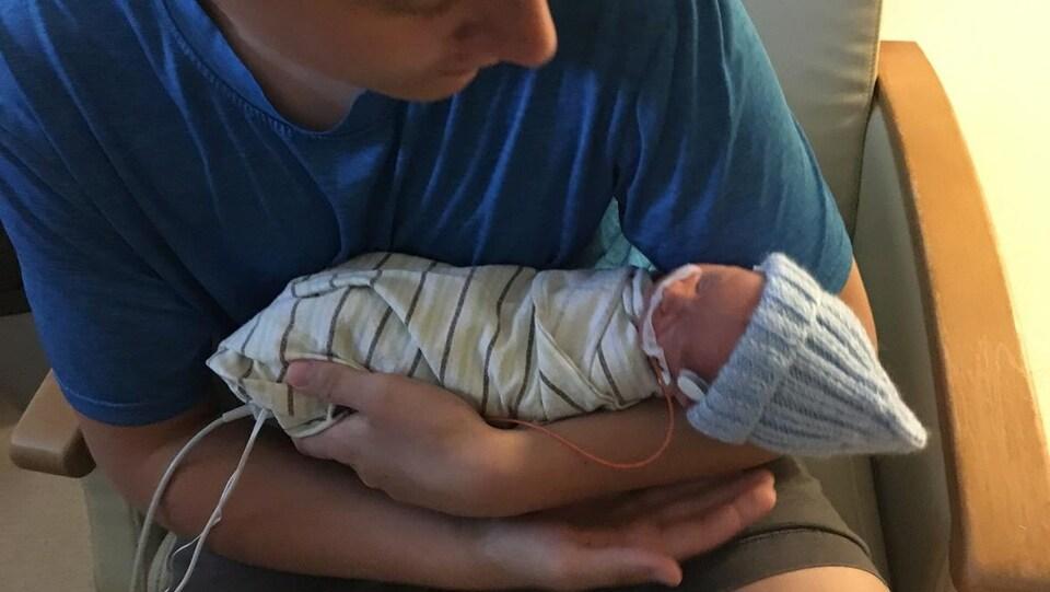 Un adolescent assis dans un fauteuil tient avec précaution un nouveau-né dans ses bras.