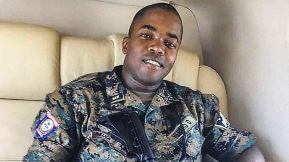 Dimitri Hérard, assis, portant un uniforme militaire et un fusil.